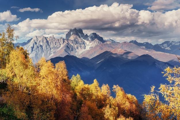 Осенний пейзаж и снежные горные вершины.