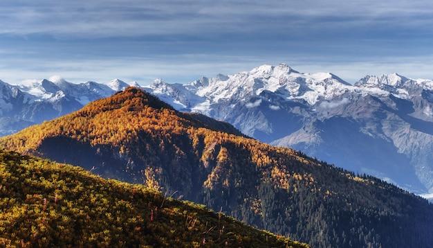 Осенний пейзаж и снежные вершины на солнце.