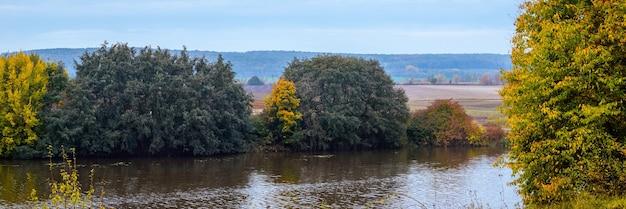 Осенний пейзаж. разноцветные деревья у реки осенью в солнечный день