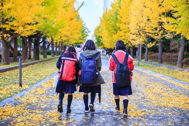 Осенний пейзаж в японии. три девушки ходят по улице. назад к школьным концепциям.