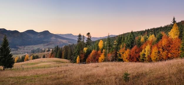 夕日の森の丘と山々の秋の風景