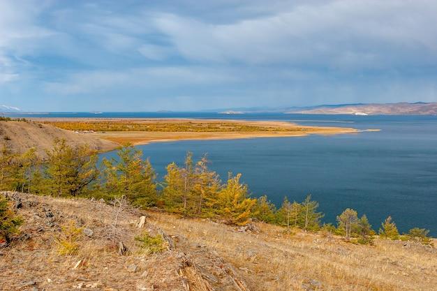 Осенний пейзаж с видом на байкал. желтые деревья и голубая вода. камни на земле. облака в небе и дождь вдали. по горизонтали.