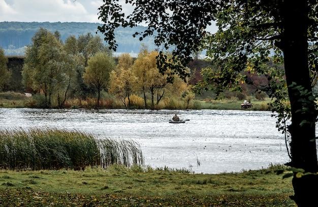 川と岸辺の木々を見下ろす秋の風景。池の真ん中でボートで釣り