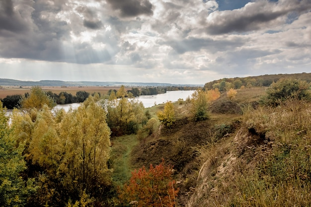 Осенний пейзаж с видом на реку у леса и скал