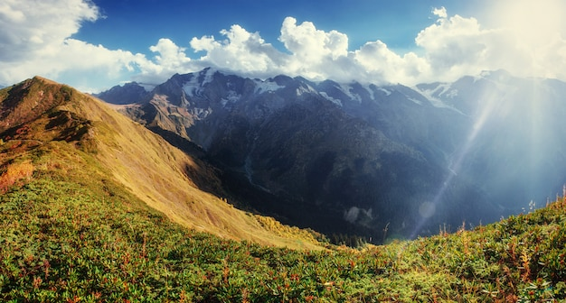 Autumn landscape and snow-capped mountain peaks.