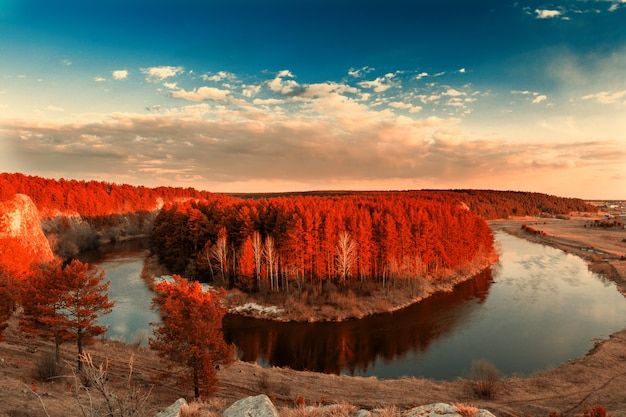 Autumn landscape. view from the cliff to the trees with red leaves and the river encircling the island.