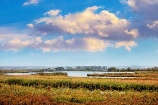 川と絵のように美しい色とりどりの雲のある秋の風景。