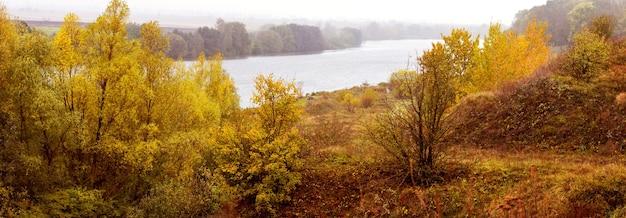 海岸の川と遠くの森、パノラマに色とりどりの木々や茂みのある秋の風景。黄金の秋
