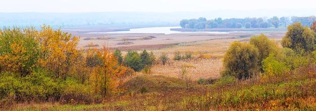 川のある広い平原に色とりどりの木々が生い茂る秋の風景、パノラマ