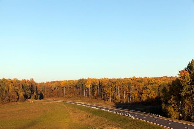 Осенний пейзаж с холмистой территорией и пожелтевшими деревьями, голубым небом и солнечной погодой. асфальтированная дорога проходит через лес