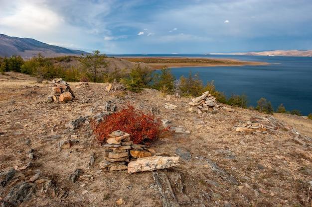 バイカル湖と前景に石の山がある秋の風景