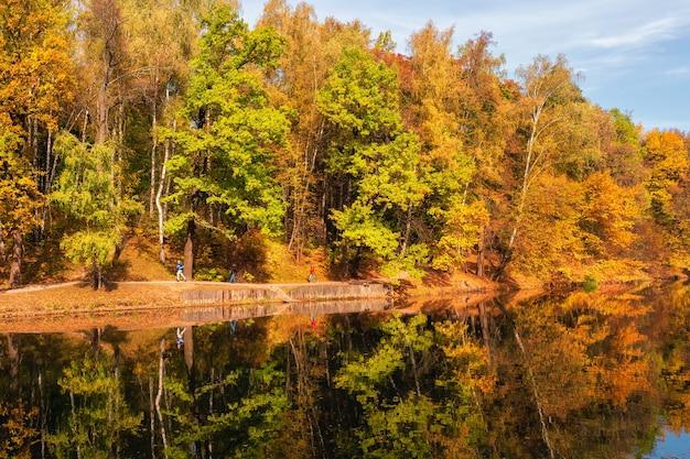 モスクワのツァリツィーノ湖のほとりに赤い木々のある秋の風景 Premium写真