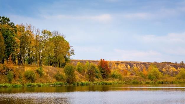 川と川沿いの森のある秋の風景。