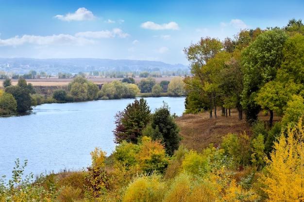 川岸に川と森のある秋の風景