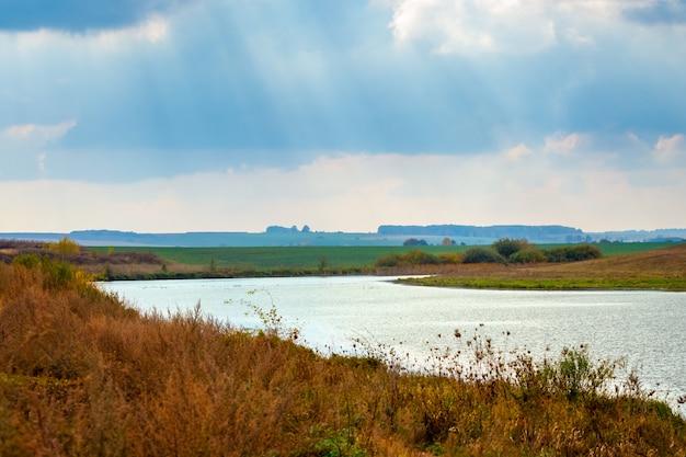 雲を突破する川と太陽光線のある秋の風景