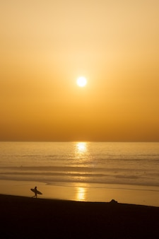 Autumn landscape with warm colors at a sunset on the beach with the silhouette of a surfer