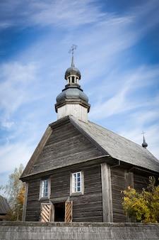 Осенний пейзаж. желтая листва на деревьях и деревенской деревянной церкви. фото высокого качества