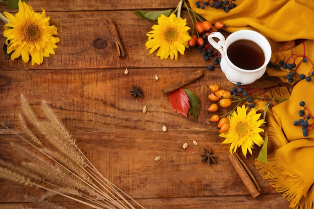 가을 레이아웃입니다. 나무 테이블 위에 차 한 잔이 놓여 있습니다. 노란색 스카프, 딸기, 해바라기 꽃이 있는 아름다운 설정. 계피 이삭과 단풍 주위. 공간을 복사합니다. 플랫 레이