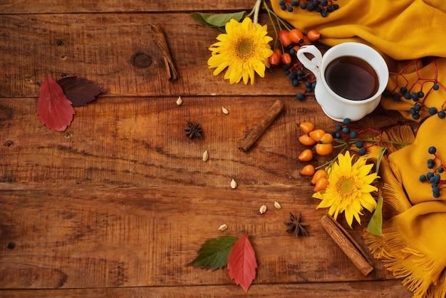 가을 레이아웃입니다. 나무 테이블 위에 차 한 잔이 놓여 있습니다. 노란색 스카프, 딸기, 해바라기 꽃이 있는 아름다운 설정. 계피 스틱과 단풍 주위. 공간을 복사합니다. 플랫 레이