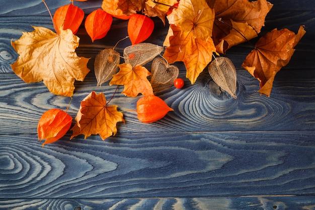 青い木製のテーブルの上の秋の葉の背景