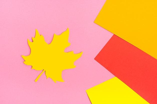 Осенний лист, вырезанный из желтой бумаги на фоне цветной бумаги