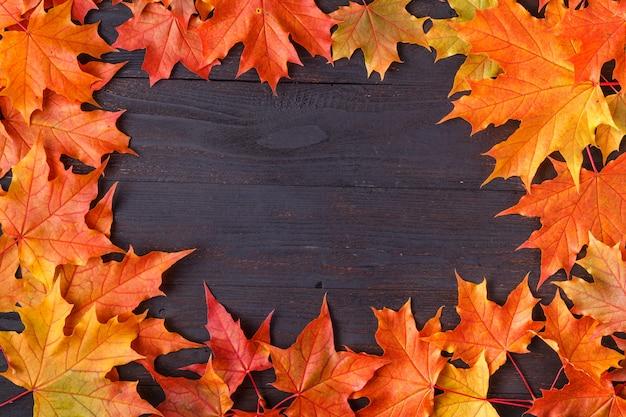Autumn leaf on wood black background orange leaf on old grunge wood deck, copy place for inscription, top view, tablet for text