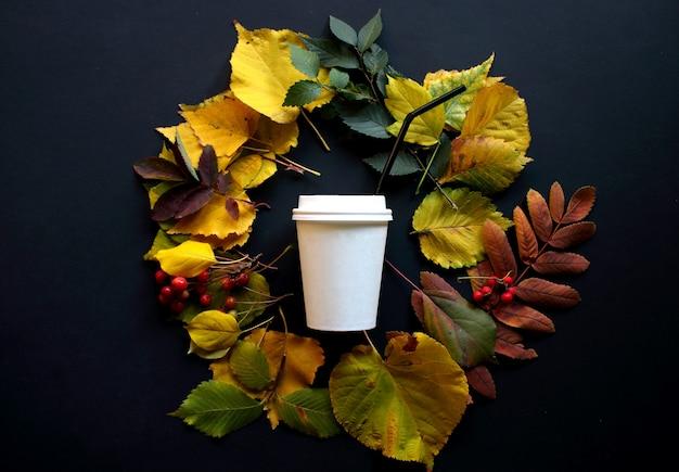 Осенние листья и одноразовая чашка кофе на черном фоне