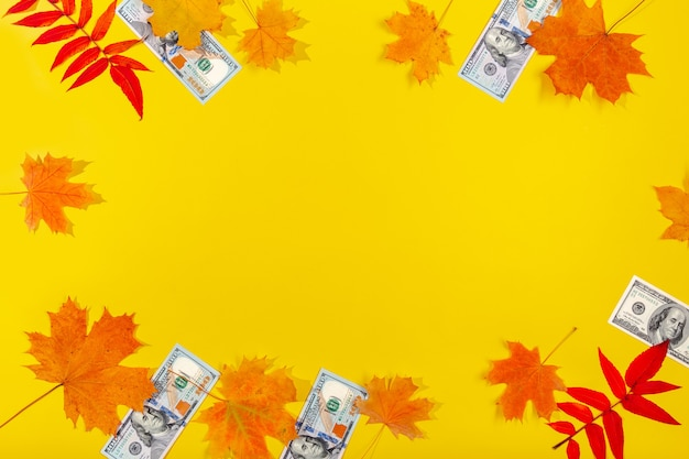 Осенние листья и банкноты доллара и евро на желтом столе