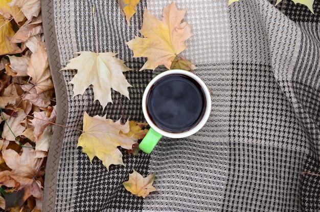 秋の紅葉と熱い蒸し一杯のコーヒーは、格子縞の格子縞の屋外にあります