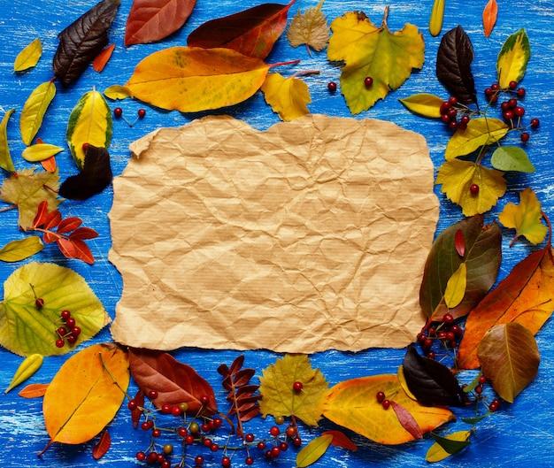 Осенние листья и бумага на синем фоне