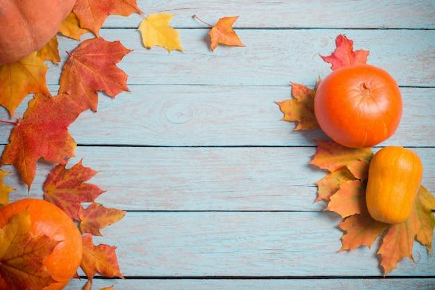 紅葉と青い木製のテーブルにカボチャ