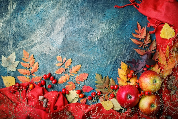 Autumn leaves, apples and berries on a dark background. autumn background with copy space.