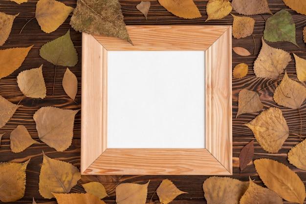 Foglie di autunno intorno al telaio sul tavolo