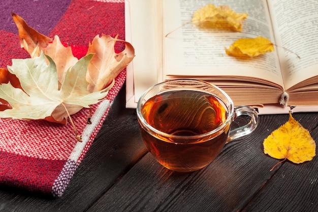 Осенние листья, книга и чашка чая