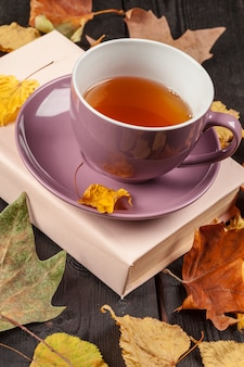 Autumn leaves, book and cup of tea