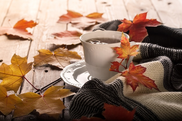 Autumn leaves and cup of tea on wooden table.