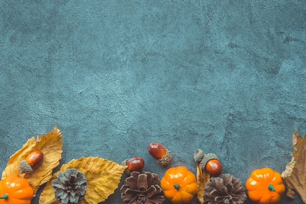 Autumn leaves, decorative pumkins, acorns and cones over blue wooden background
