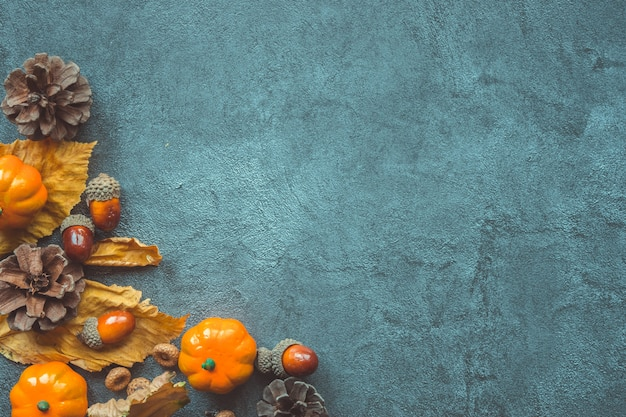 Autumn leaves, decorative pumkins, acorns and cones over gray background