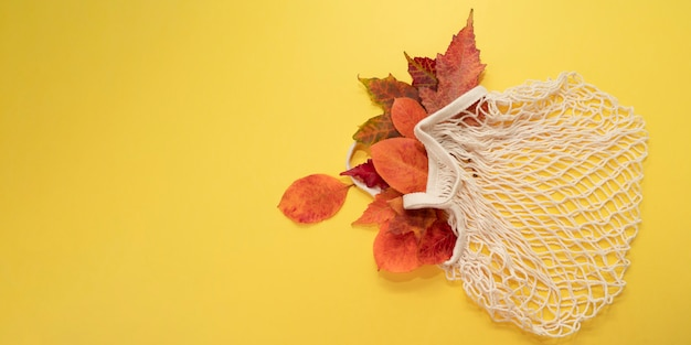 Autumn leaves in eco mesh bag on bright yellow background.