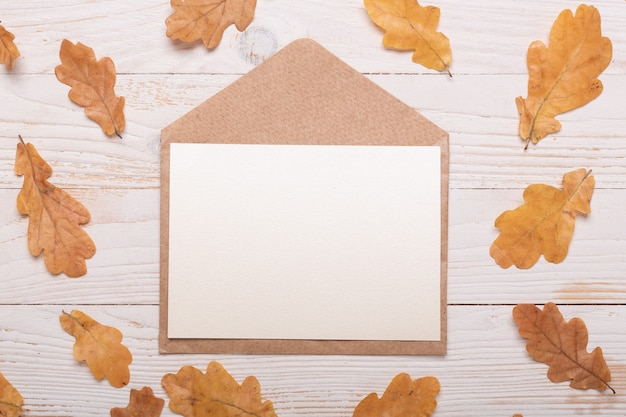 Autumn leaves and envelope on a white wooden background. flat lay, top view, copy space.