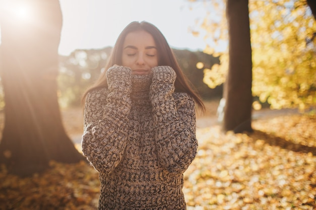 Autumn leaves falling on happy young woman in forest. portrait of very beautiful girl in fall park
