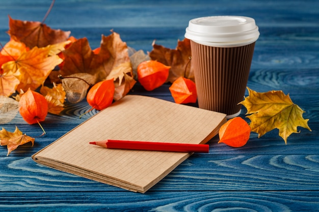Autumn leaves, hot steaming cup of coffee and on wooden table background. seasonal, morning coffee, sunday relax and still life concept