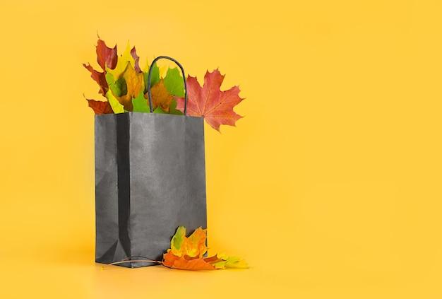 오렌지 배경에 가방에 단풍. 레이아웃의 계절 구성, 텍스트 위치가 있는 템플릿. 컨셉 - 가을 세일, 쇼핑 여행