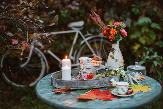 Autumn leaves lie on a wooden antique round table with crockery cups and cookies burning candle.