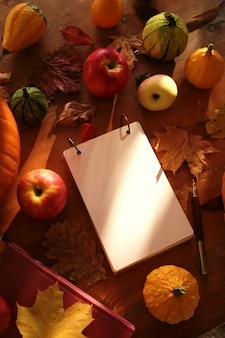 Autumn leaves, notebook, apples and pumpkins