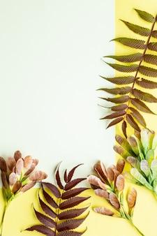 Осенние листья на желтом фоне. осенняя концепция с местом для текста