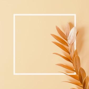 Осенние листья на пастельно-розовом фоне осенняя концепция с местом для текста в белой рамке
