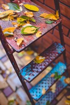 Осенние листья на садовой металлической лестнице. осенний фон.
