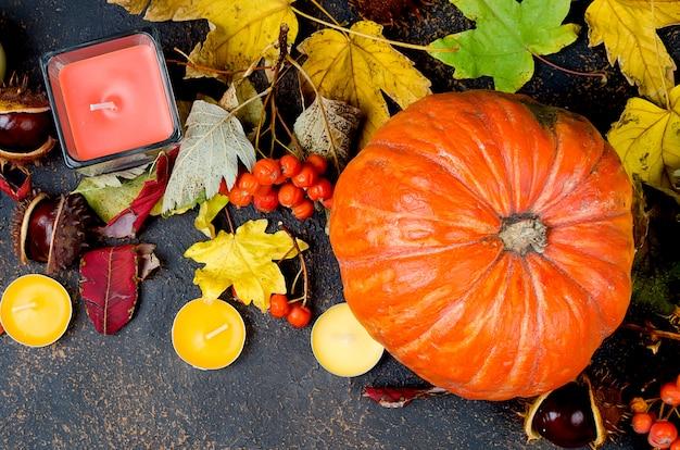 Autumn leaves, pumpkin, chestnuts, candles on a dark