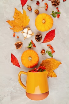 Autumn leaves, pumpkins, berries pour out of a pitcher on a grey background